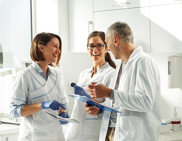 Dentist and dental team members laughing together